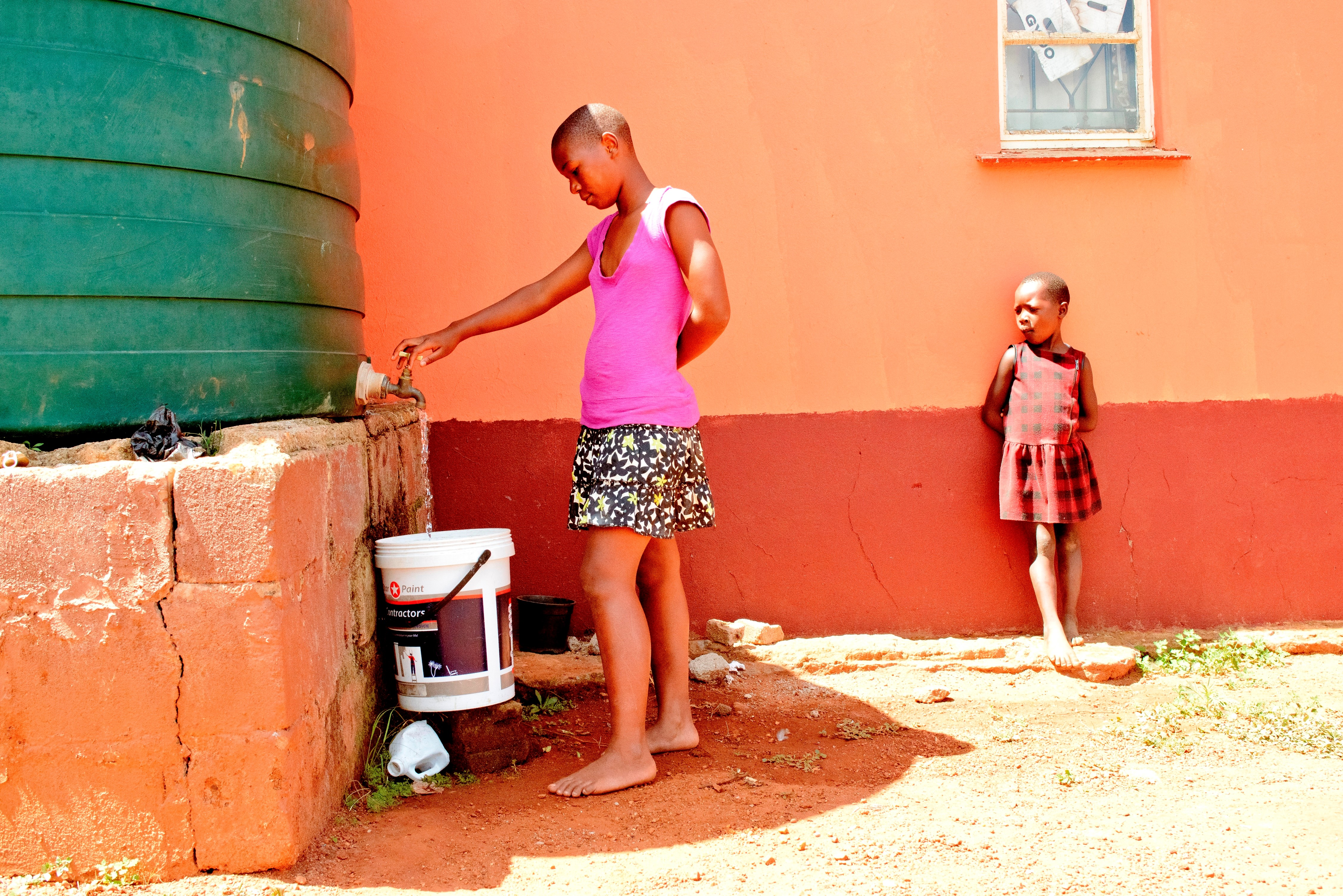 A girl from Mbabane's family strengthening program fetches water from their new harvesting tank. Photo: SOS Children's Villages